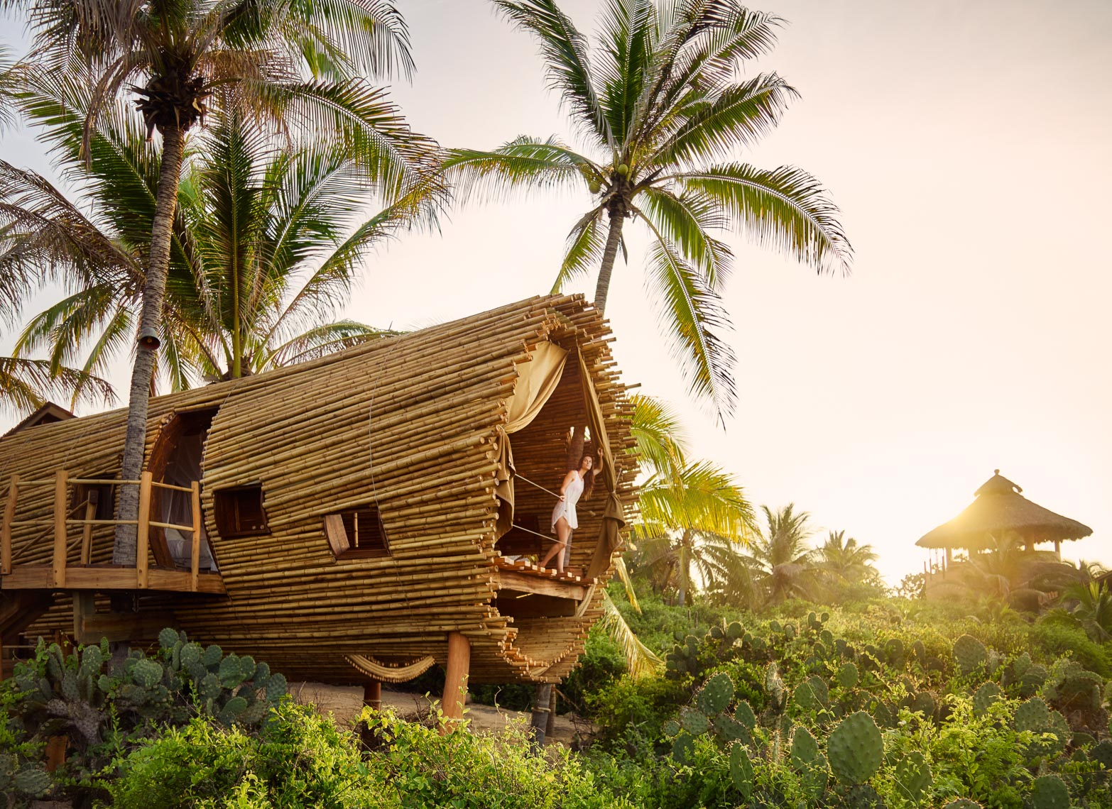 Kevin Steele - A woman in a bamboo treehouse at an eco-resort hotel