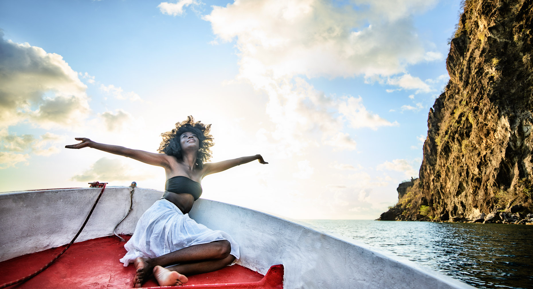 Kevin Steele - woman spreads her arms in joy on a boat
