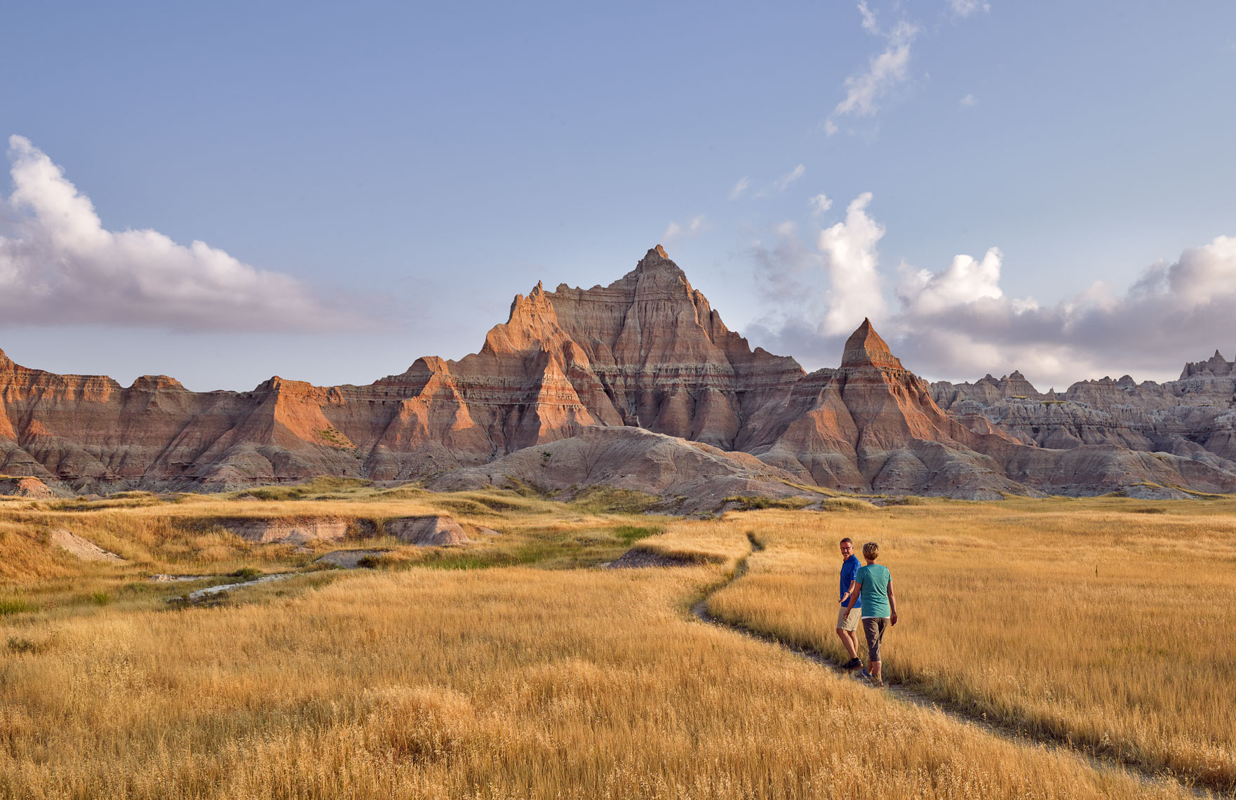 A couple hike along a trail in the landscape of the Badlands