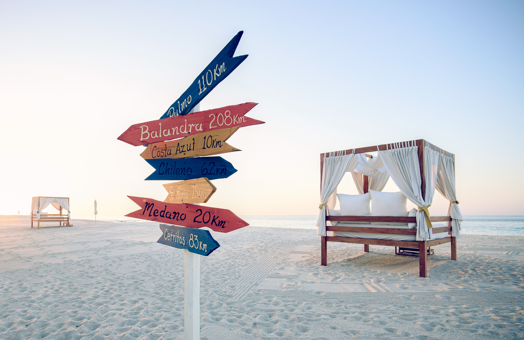 Kevin Steele - A signpost with travel destinations on a beach