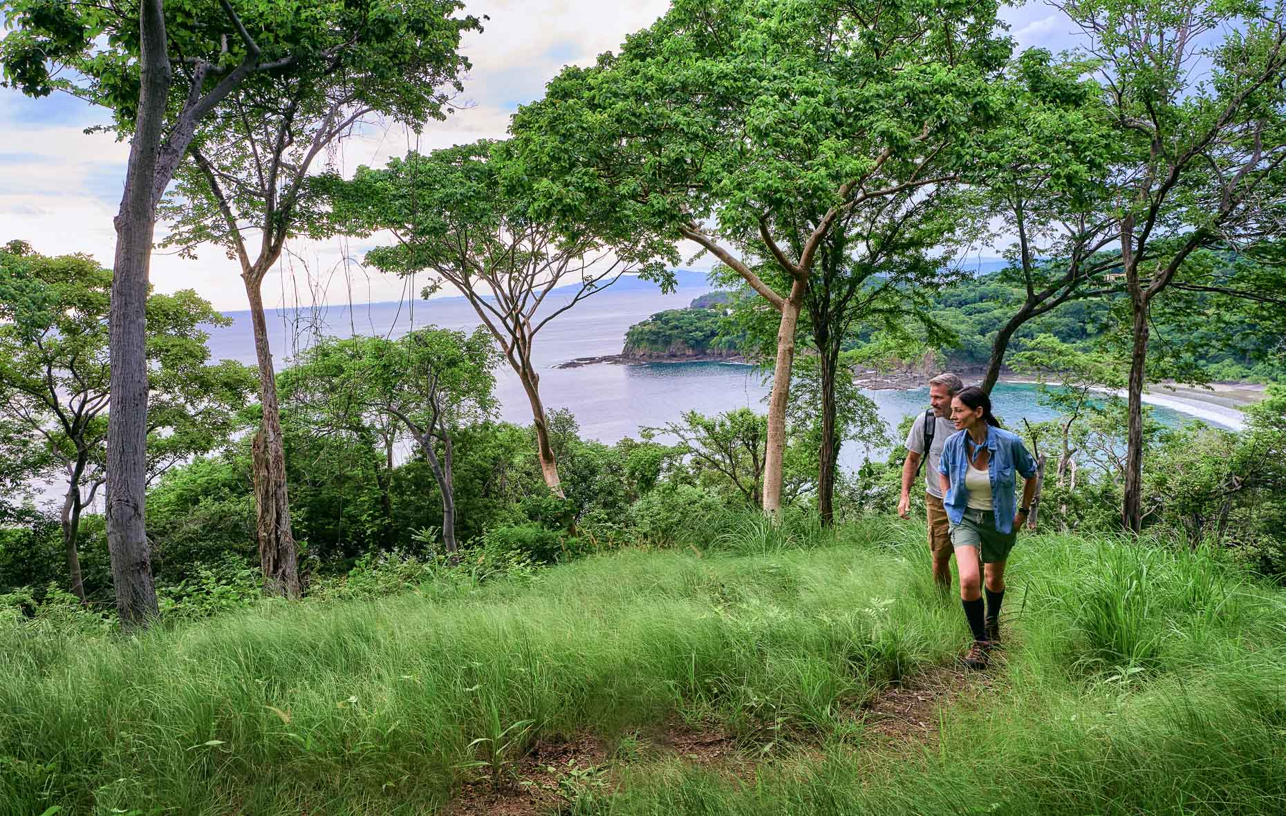 Kevin Steele - a couple hike among lush green oceanfront hills
