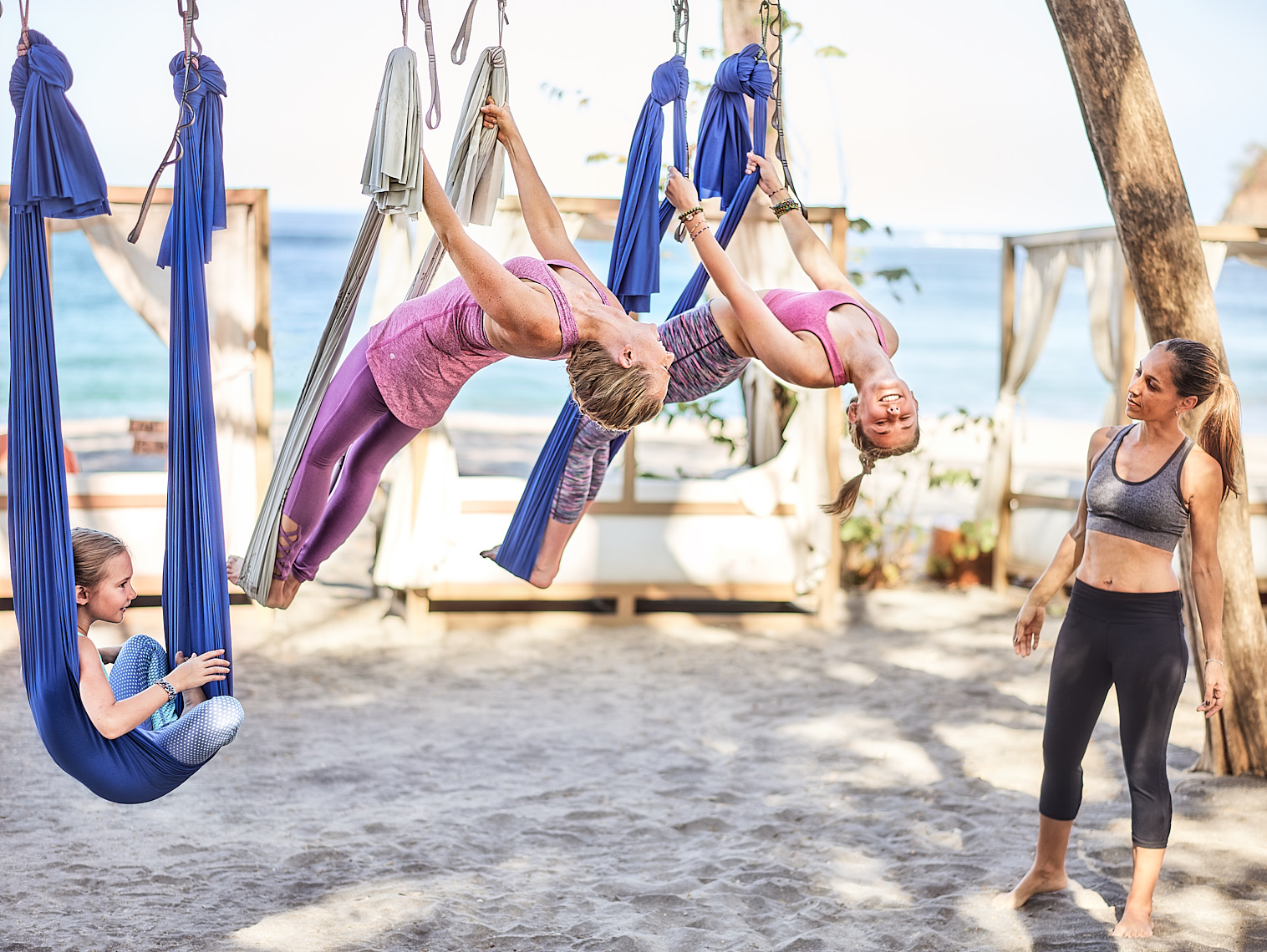 Mother and daughters aerial yoga fitness on the sand