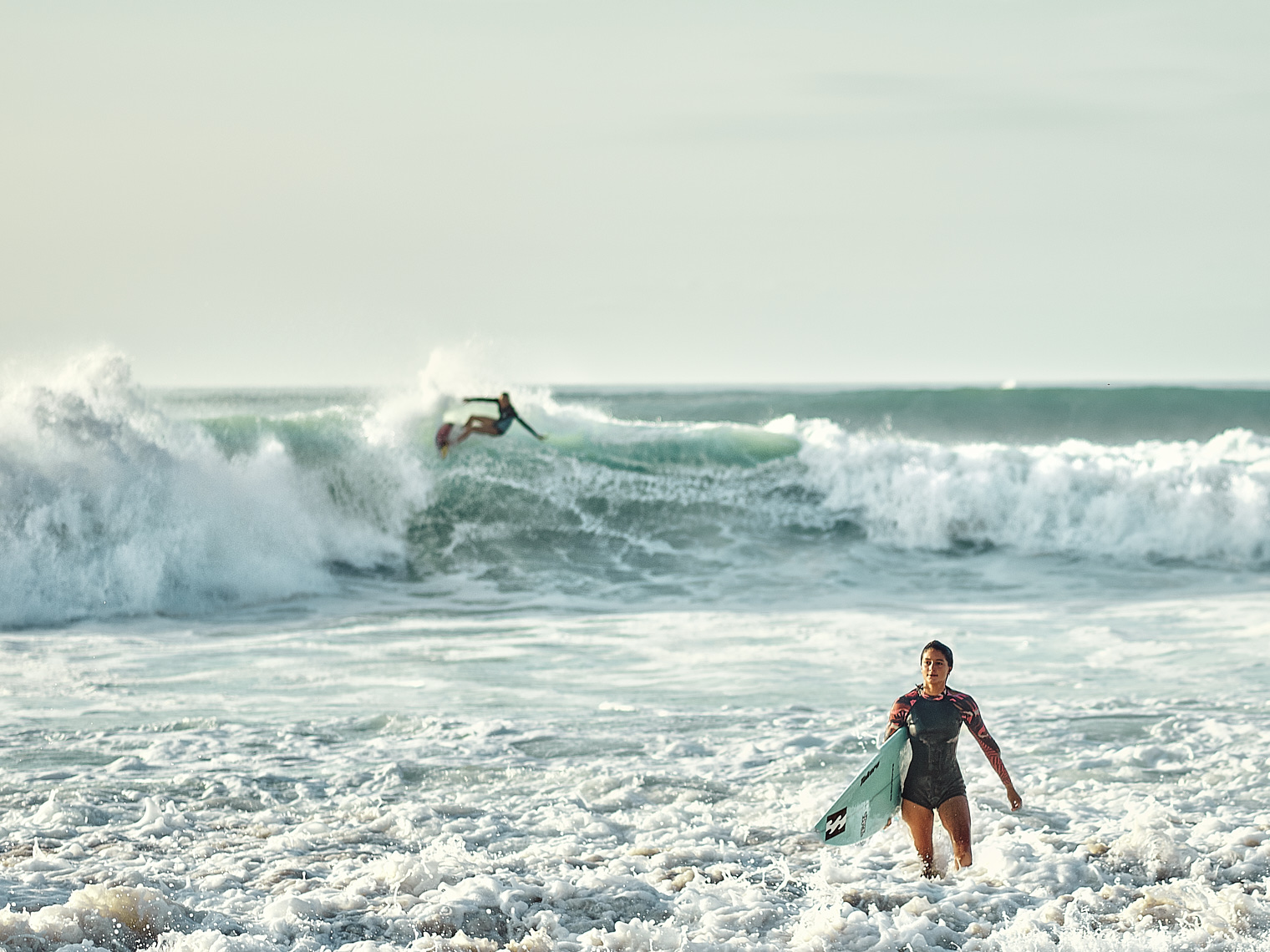 A young woman surfer emerges from the big waves