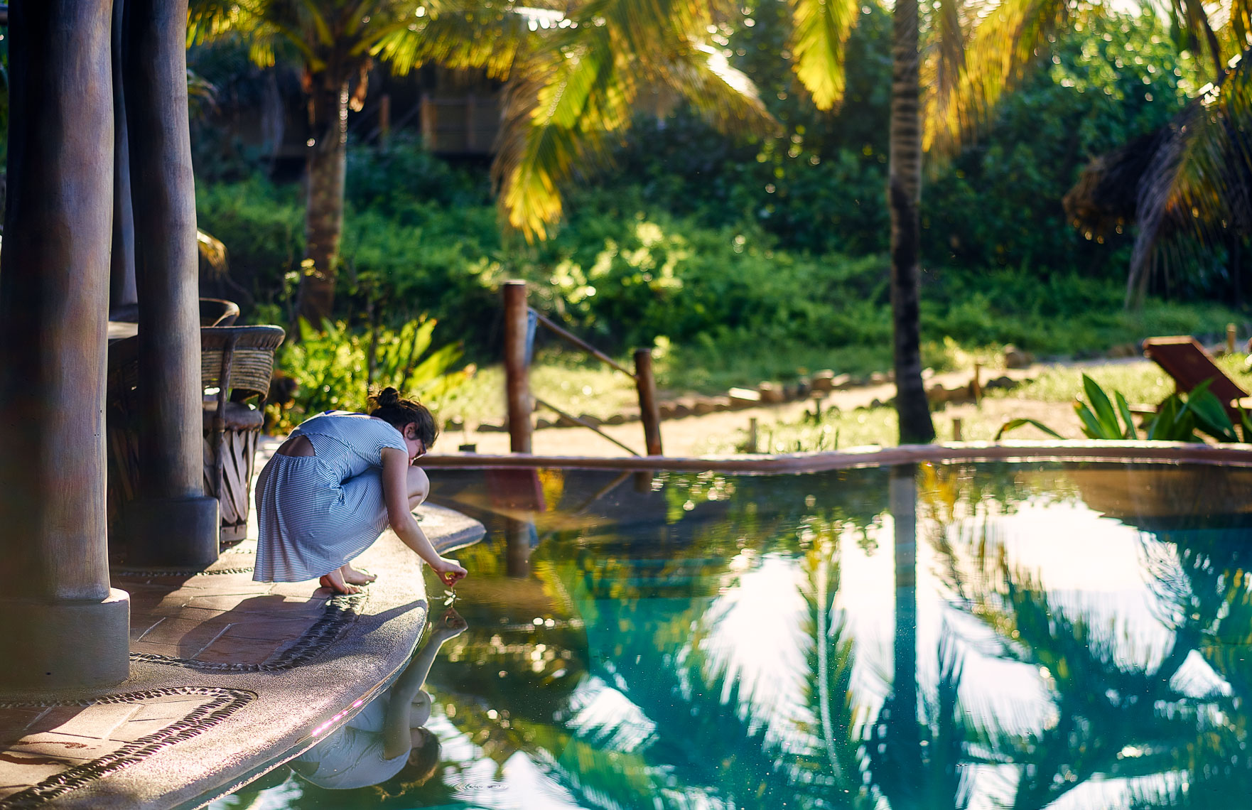 A young girl at the pool of a  beautiful eco resort