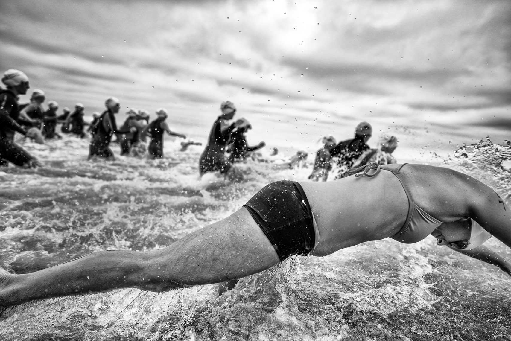 Kevin Steele - a woman dives into the ocean at a triathlon