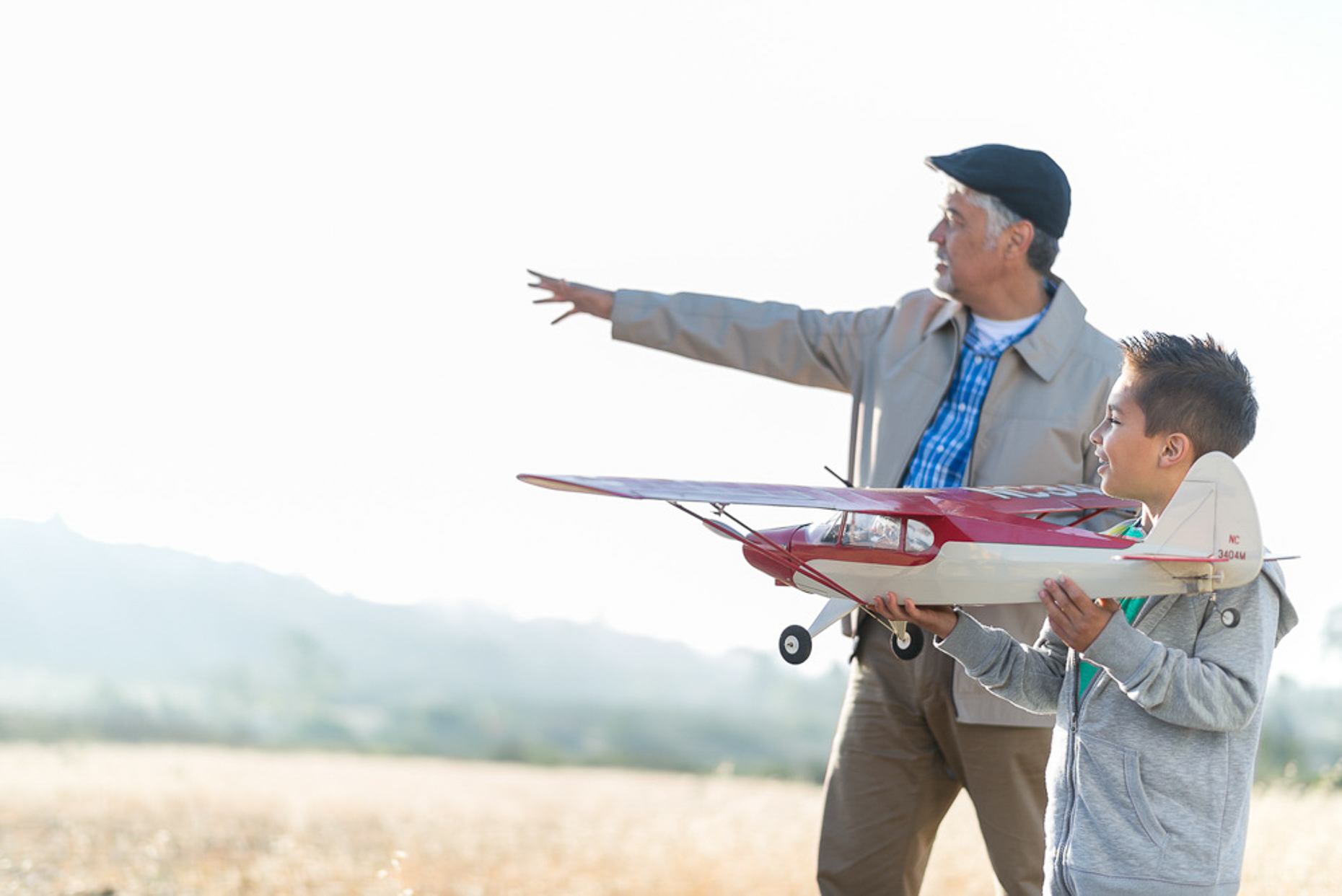 Kevin Steele - An elder man helps his grandson fly a model airplane