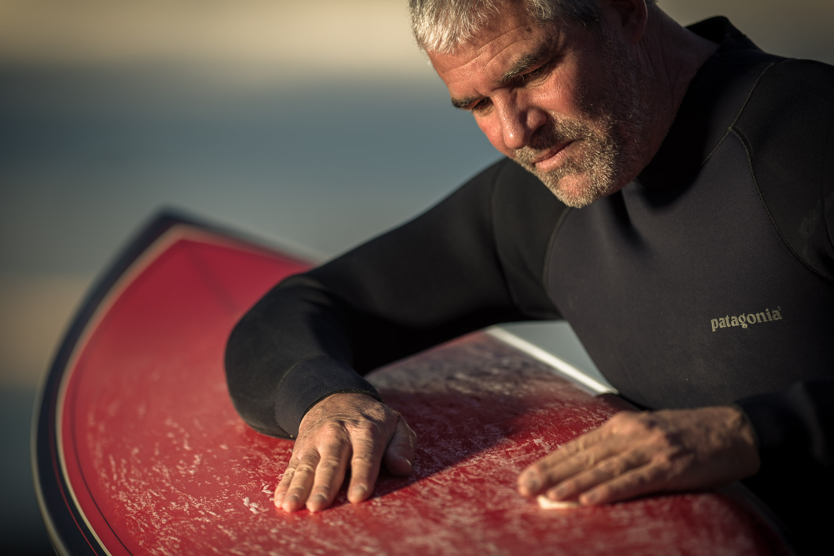 Kevin Steele - an elder surfer waxes his board at twilight